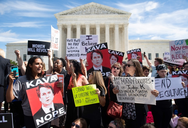 Demonstrators protesting against Judge Brett Kavanaugh's nomination as an Associate Justice on the Supreme Court hold a rally outside the US Supreme Court in Washington, DC, September 28, 2018. - Kavanaugh's contentious Supreme Court nomination will be put to an initial vote Friday, the day after a dramatic Senate hearing saw the judge furiously fight back against sexual assault allegations recounted in harrowing detail by his accuser.